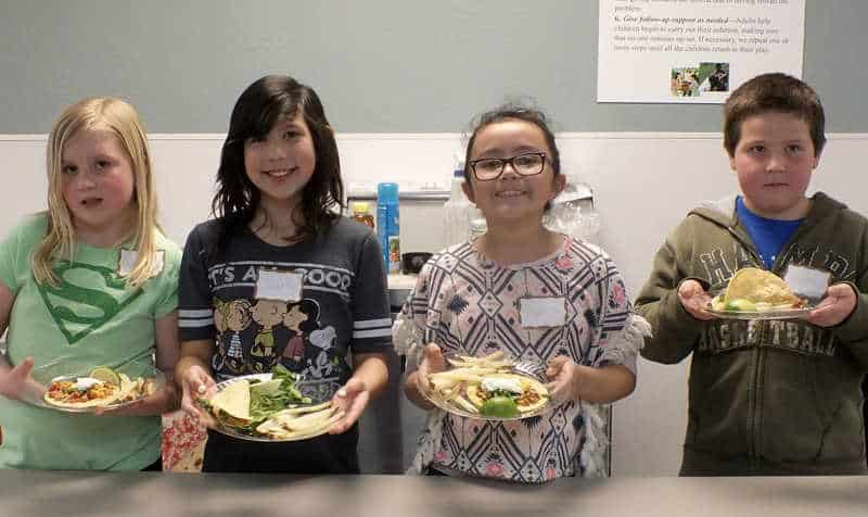 inline image showing four diverse children wearing name tags, smiling and holding a plate of food