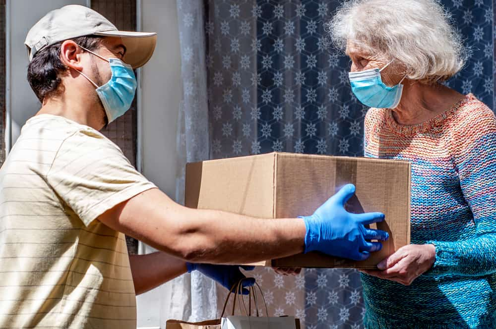masked volunteer dropping off food to an elderly woman