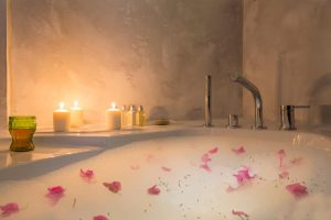 bath with bubbles, flower petals and candles